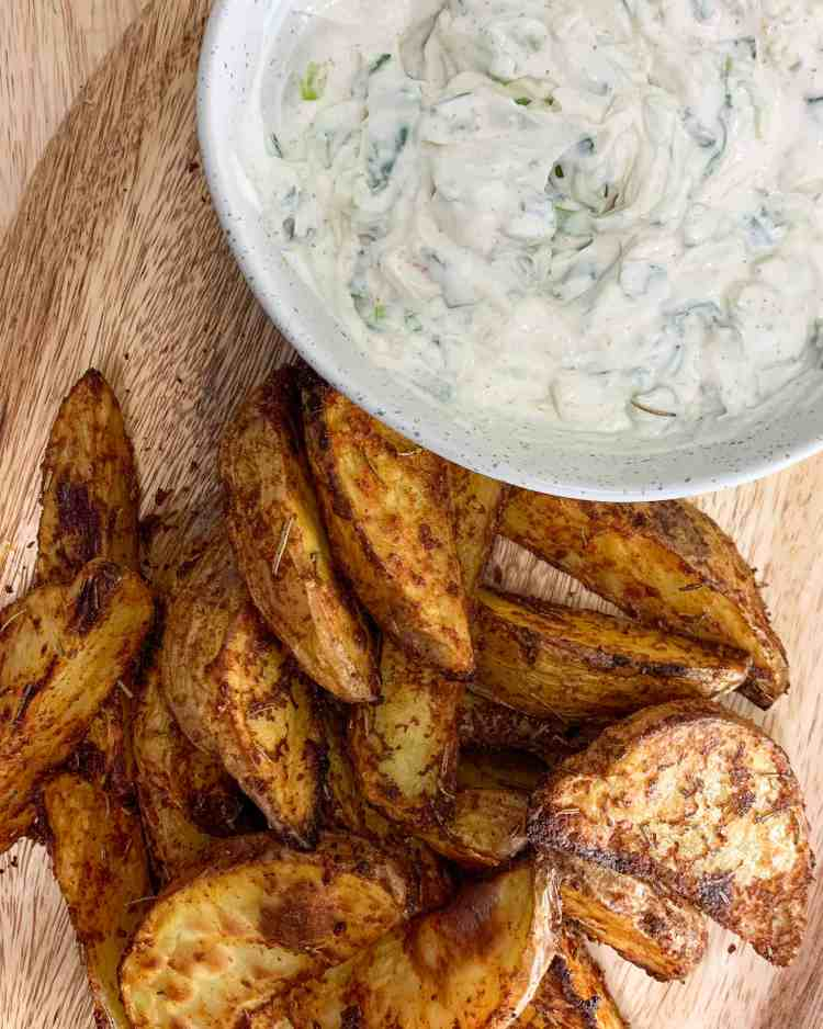 A bowl of sour cream and onion dip with a pile of crispy wedge potatoes on the side.