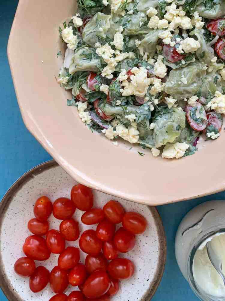 Summer tortellini salad with a bowl of cherry tomatoes on the side.
