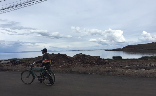 Peru Bolivia border - man walking with his bike with view from desaguadero in background