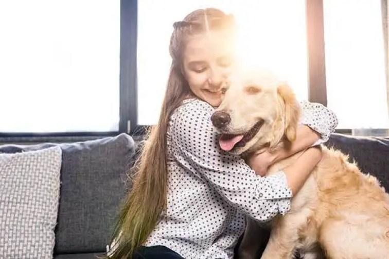 a lovely little girl hugging her dog