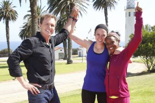 "Host Phil Keoghan congratulates Amy DeJong (left) and Maya Warren (right) for winning Season 25 of ""The Amazing Race."""