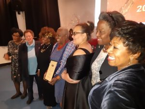 Jetty Mathurin met haar oorkonde, geflankeerd door andere topvrouwen van Surinaamse origine