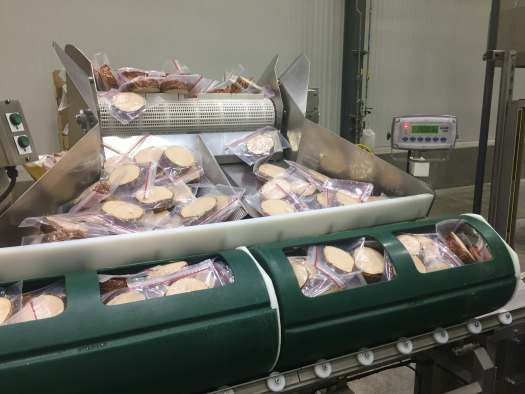 Deli meat packages coming up from Vertical Hopper to be loaded into two 36 inch HPP Baskets