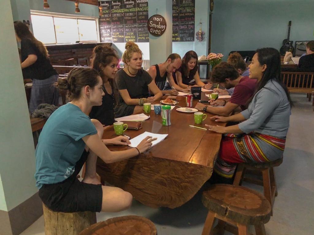 Pessoas conversando e tomando café da manhã ao redor de uma grande mesa de madeira no Song of Travel Hostel, em Mianmar