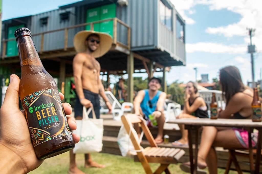 Área externa do Innbox Hostels, com várias pessoas conversando num dia de sol. No primeiro plano, uma mão segura uma cerveja Innbox Beer Pilsen
