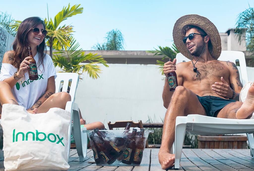 Duas pessoas, tomando a Innbox Bier Pilsen, conversam deitadas em espreguiçadeiras. No primeiro plano, uma ecobag do Innbox hostel.