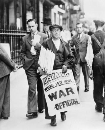 """Mężczyzna na ulicy z plikiem gazet pod pachą, trzymający w drugiej ręce rozwinięty biały plakat z napisem: """"DISPATCH / SPECIAL LATE NEWS / WAR – OFFICIAL"""". W tle przechodnie."""