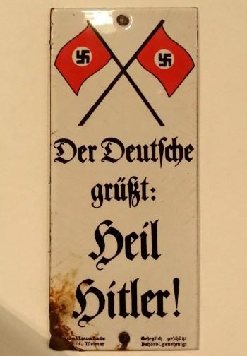 """Wąska, pionowa, emaliowana tabliczka przymocowana do ściany dwoma gwoździami (u góry i u dołu). U góry dwie skrzyżowane nazistowskie flagi (czerwone ze swastyką po środku), a niżej zapisano pismem gotyckim po niemiecku: """"Niemiec pozdrawia: Heil Hitler!"""""""