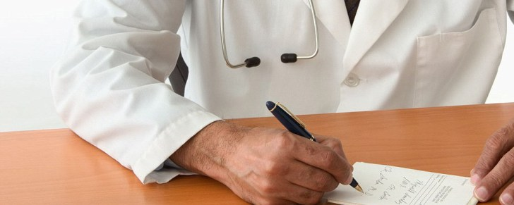 Mid section view of a male doctor writing a prescription