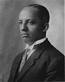 128px-Dr._Carter_G._Woodson_(1875-1950),_Carter_G._Woodson_Home_National_Historic_Site,_1915._(18f7565bf62142c0ad7fff83701ca5f6)