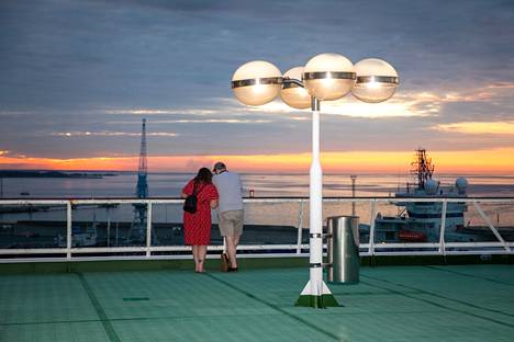 The Finnish-Spanish couple Aina Palmer and Markku Sahakangas watched the sunset on the deck of the ship in the port of Tallinn.  They booked the cruise just a few days before departure in honor of Sahakangas 'vacation.