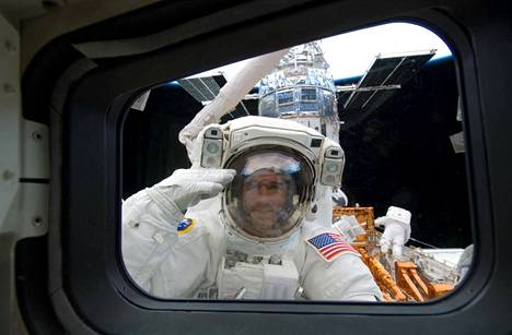 Astronauts Michael Good and Mike Massimino (right) took care of Hubble on the last maintenance flight in 2009. On a space walk, Good greeted the shuttle crew through the window.