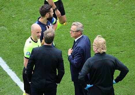 English referee Anthony Taylor discussed the situation with both teams after the situation.  The closest in the picture to Taylor are the Danish and Finnish head coaches Kasper Hjulmand and Markku Kanerva and the Captain Tim Sparv.