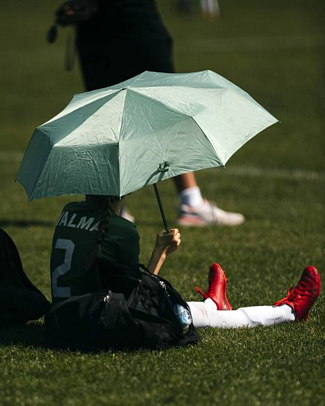 An umbrella protected the player from the sun in a hot tournament.