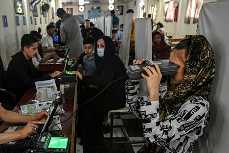 The woman looks through an optical biometric reader to submit her passport application.