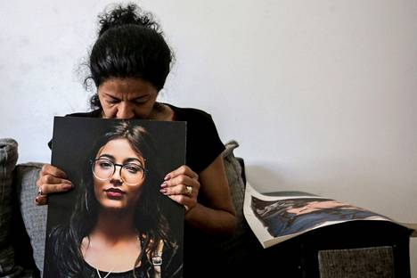 Beirut-based Mona Misto hugs a picture of her daughter Rawan, who died in the blast at the age of 20.