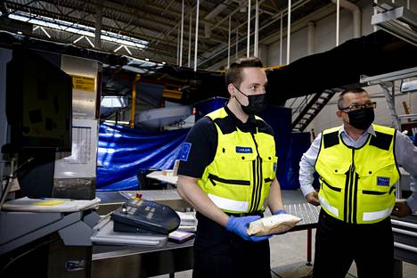 Customs inspector Aleksi Laikari examines inspected parcels in the Customs inspection area at the Post's parcel sorting center in Vantaa.  On the right, Mika Pitkäniemi, Head of Aviation Customs.