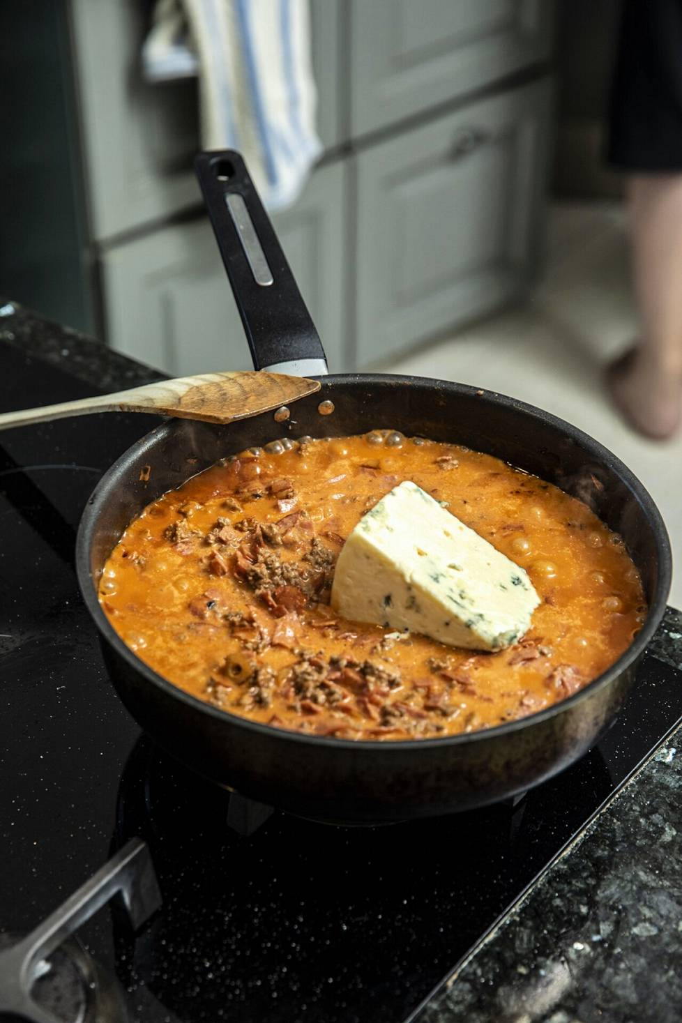 Mikko Kivinen adds a thick slice of blue cheese to his minced meat pan.