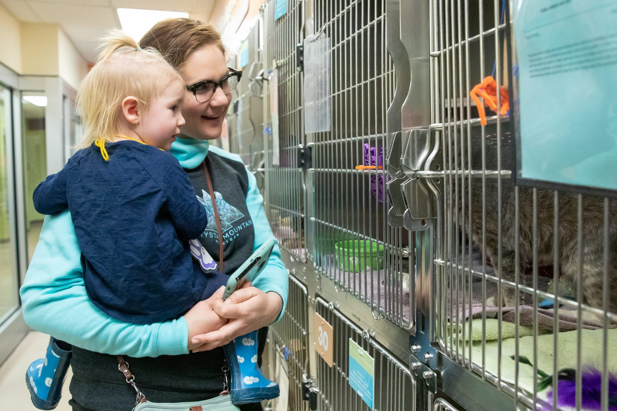 Mom and child looking in a kennel at HSHV
