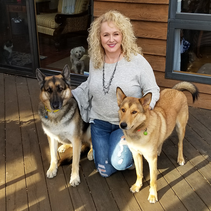 Nicole Moore Johnson with her two dogs, and another dog and cat in the background