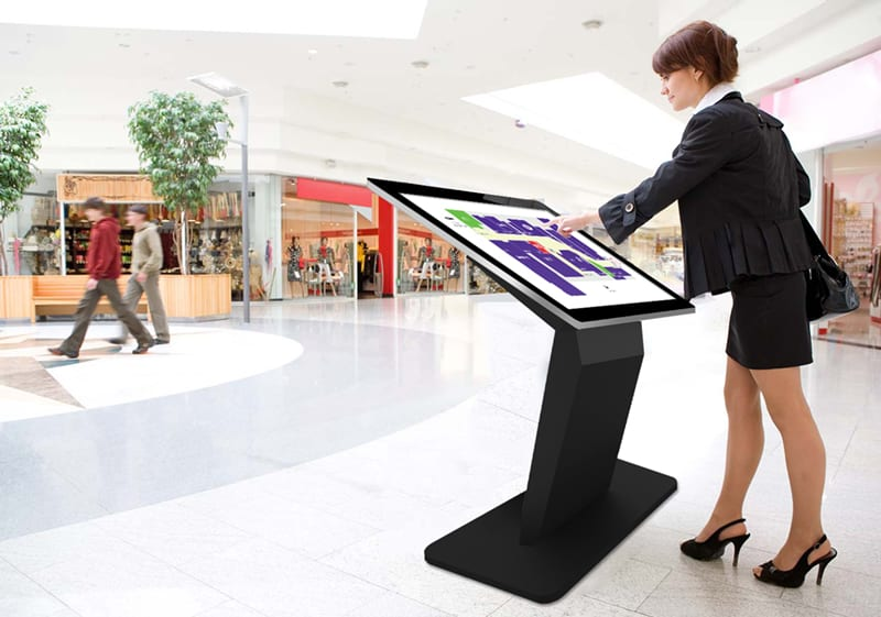 Lady interacting with a digital signage kiosk