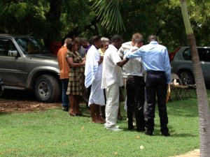 Sadrac (dressed in all white) and other church members from Quisqueya Chapel pray over the youth who were baptized. Photo by Karen Broyles.