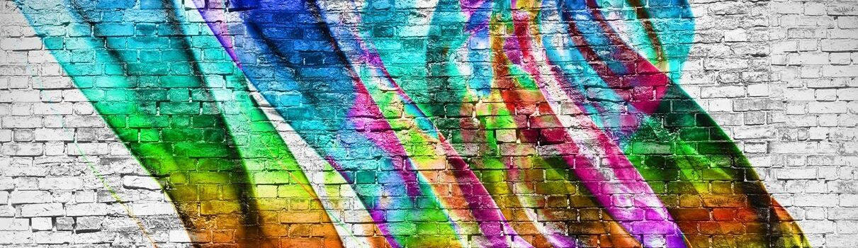 Photo of rainbow color abstract mural on white brick.