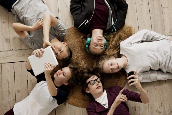 Teenagers lying on floor with Ipad and mobile