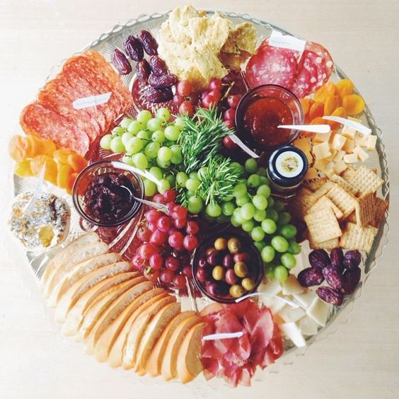 A wide array of meats, cheeses, fruit, and crackers offers variety.