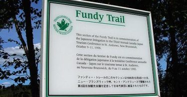 A trilingual sign commemorating a section of the Fundy Trail.