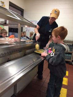 Nutrition service staff member serves mac and cheese to a student.