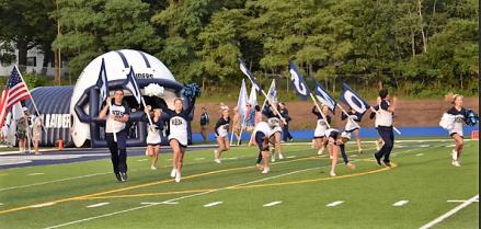 Cheer team running onto the stadium field.