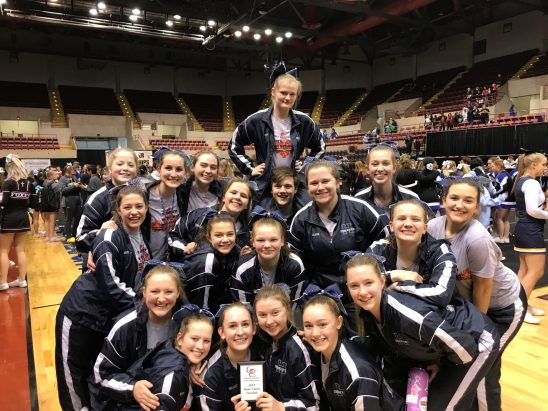 Cheer and stunt team pose with their 5th place win at state.
