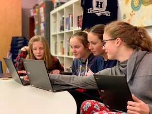 A group of girls working together with their laptops.