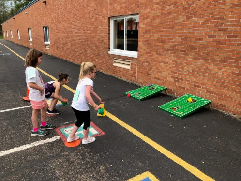 Several students playing a bean bag toss.