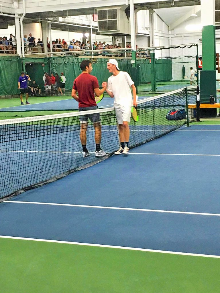 Boys high school tennis players shaking hands after a match at the State Tournament.