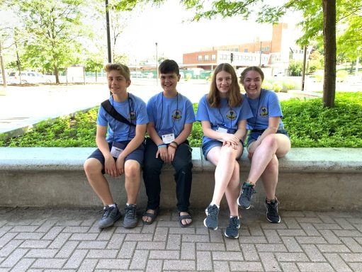 Hudson students taking a rest on a bench in the Hudson t-shirts.