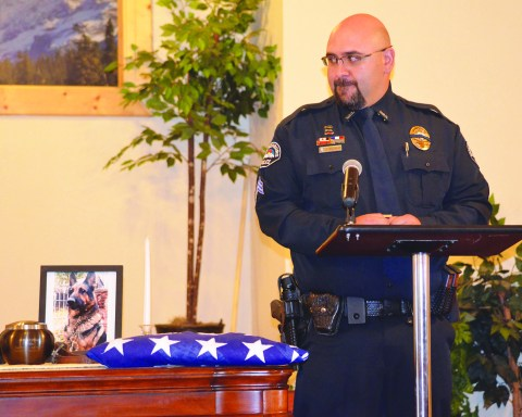 Sergeant John Salazar looks at the photo of Atos on the altar.  Photo by Eric Mullens.