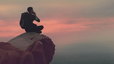 A man sitting on the edge of a cliff