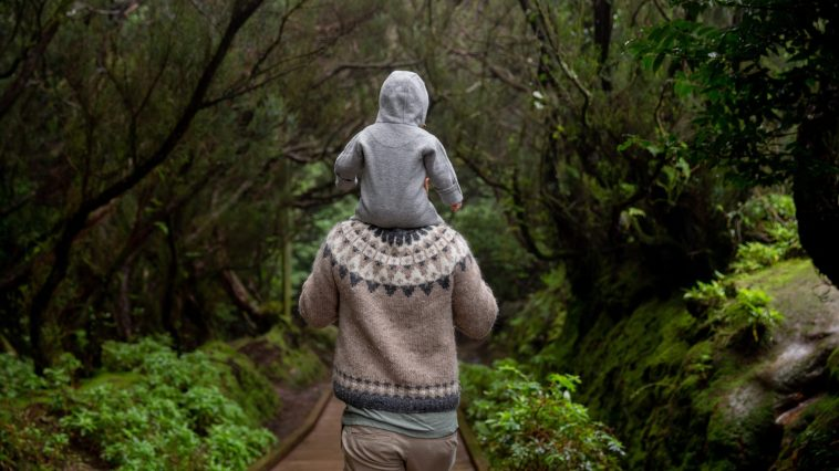 man walking with a baby on shoulders