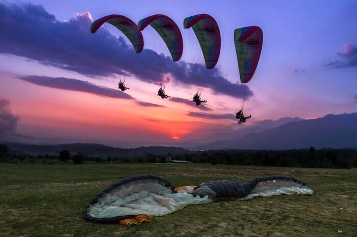 Paragliders soaring up high in the sky in Bir Billing