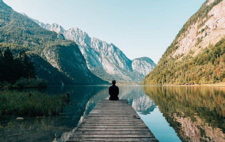 Imágen de hombre sentado de espaldas, contemplando un bello paisaje con montaña y lago, representado la meditación budista y mindfulness que aplica Hugo Filippe en su psicoterapia