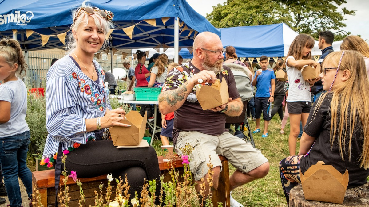 A group of people sit eating from cardboard takeaway boxes at the outdoor feastival event. One person from the group wears a blue top and smiles directly at the camera.