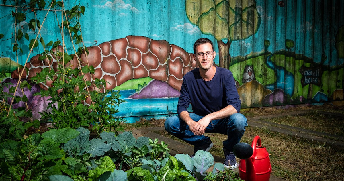 Photo shows a person crouching down next to an abundant vegetable garden and a colourful mural wall.
