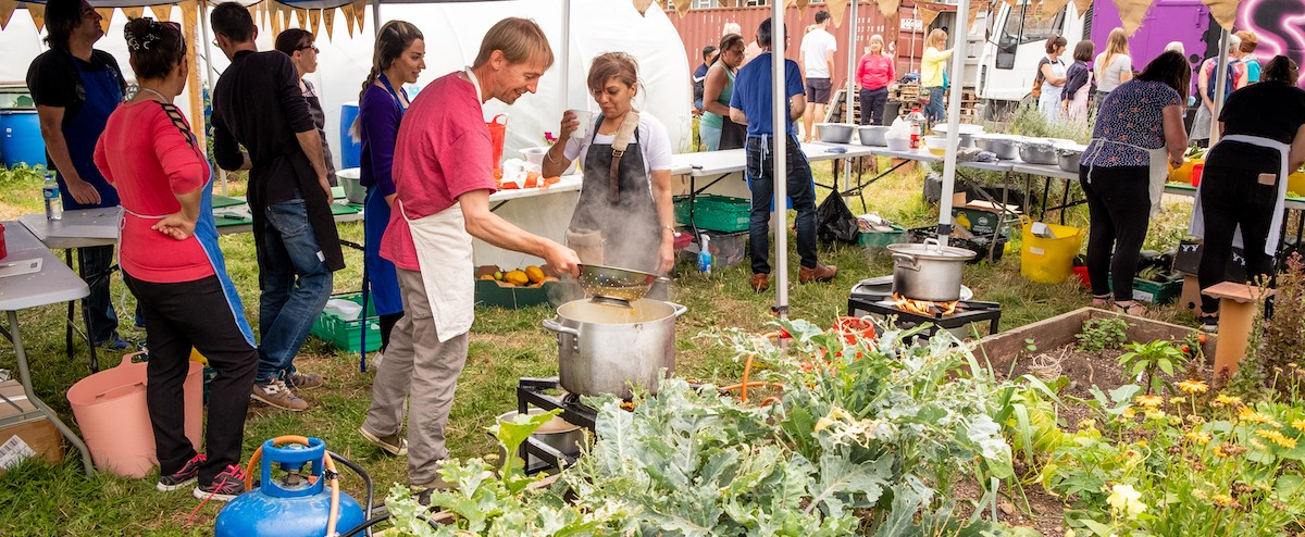 Photo showing a person tending to a large pot of food at an outdoor event. The person is surrounded