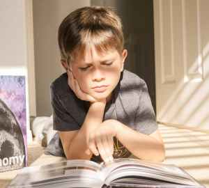 a boy reading a book on the floor