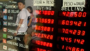 A picture shows the reflection of a man looking at foreign exchange rates at a money changer in Manila.