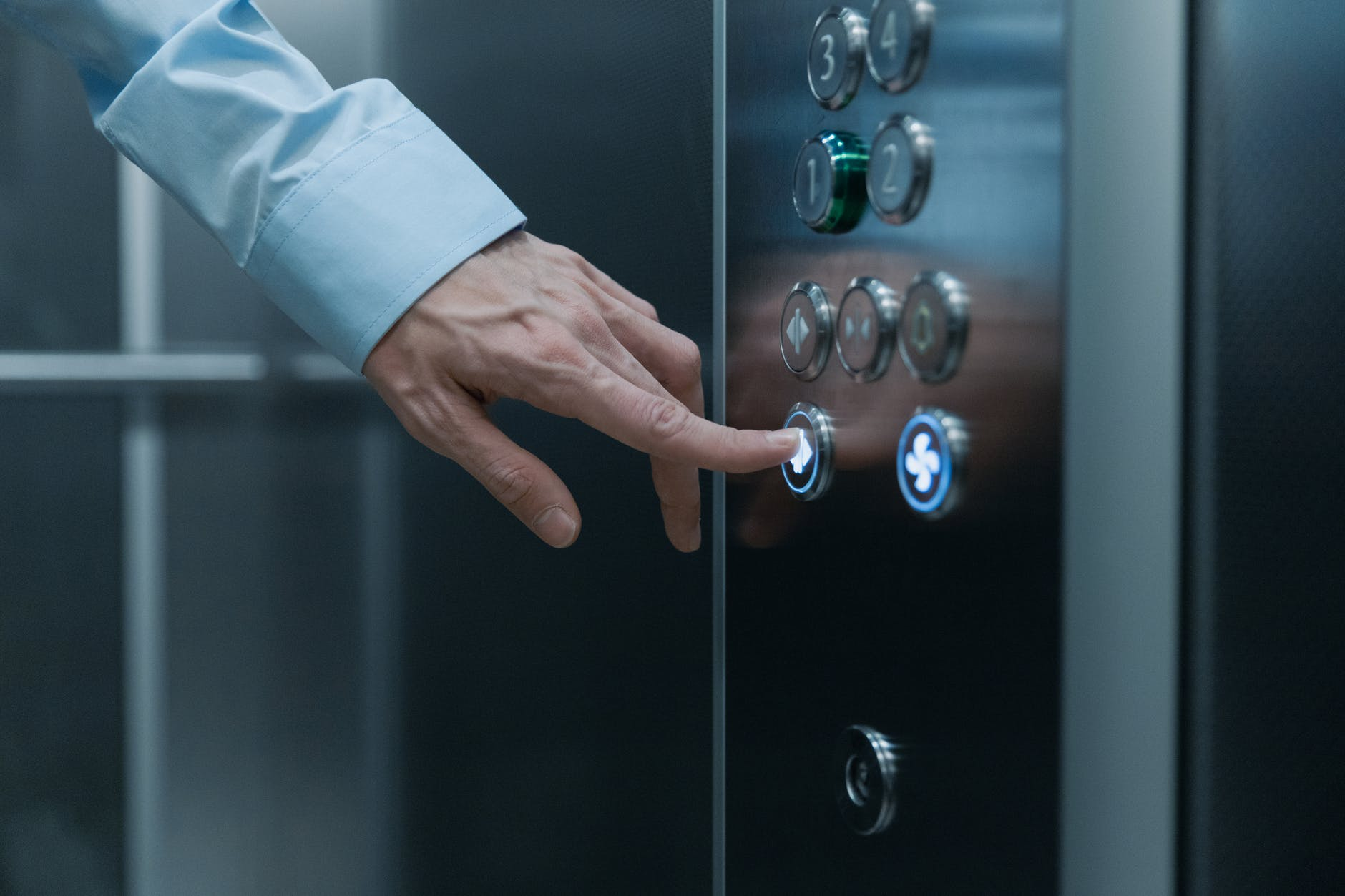 close up shot of a hand pressing an elevator button