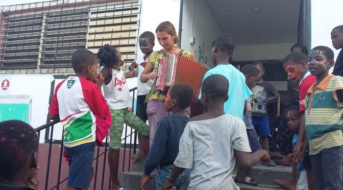photo avec élodie jouant de l'accordéons sur les marches de l'orphelinat et quelques orphelins qui l'écoutent