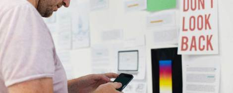 Product manager looking at iPhone while standing in front of wall of product planning notes.